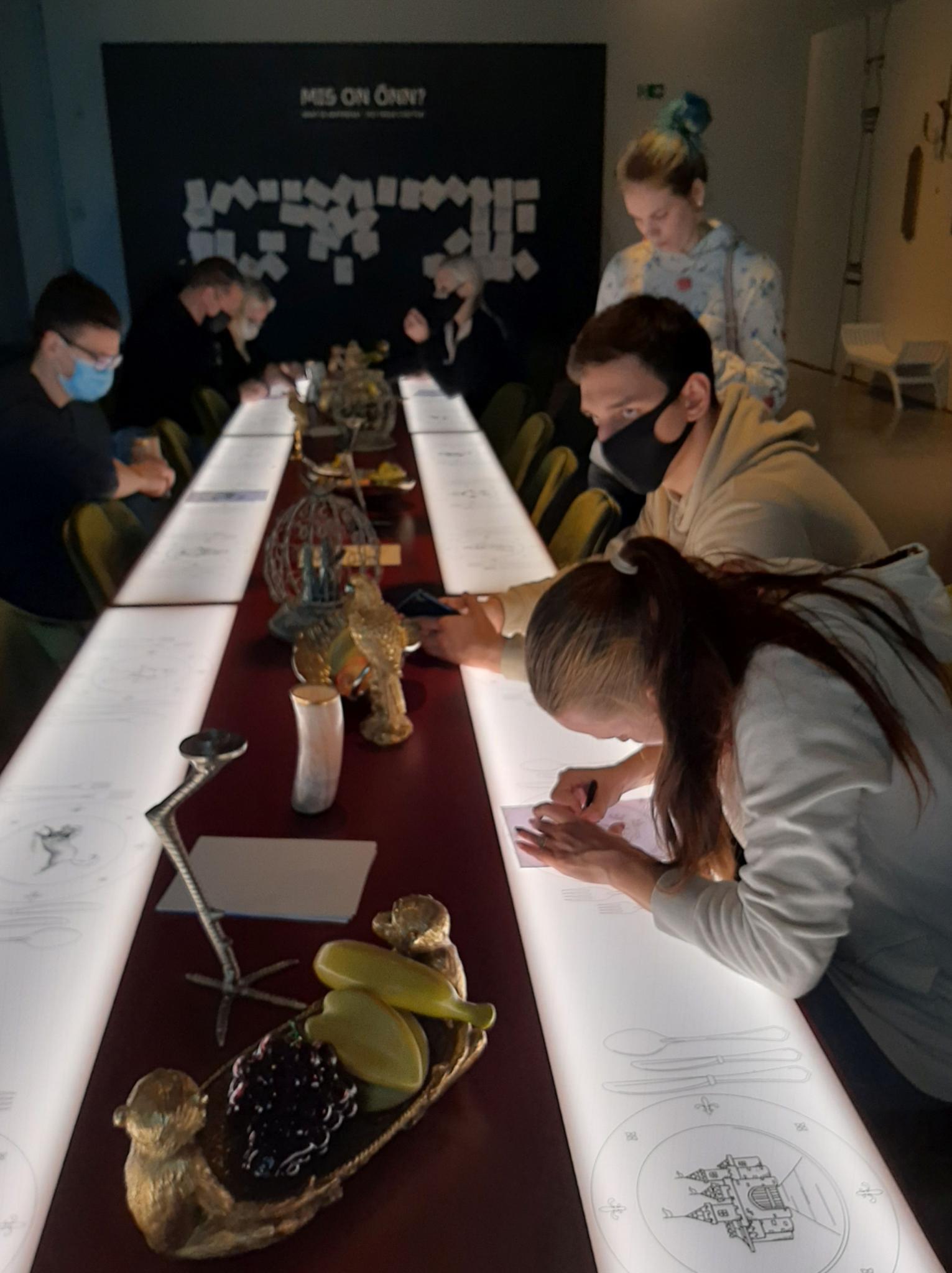Õpilased tegutsemas  helendava laua taga. Taustal sein teemal