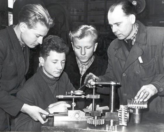 Õpilased uurimas hammasrattaid (mustvalge foto)