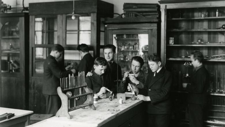 Õpilased katseklaase leegil soojendamas (mustvalge foto)