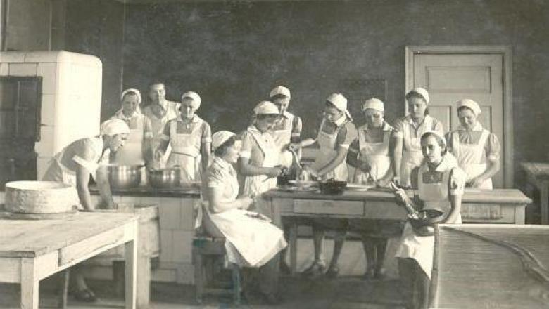 Palju naisi köögis valgete kitlite ja rätikutega  (mustvalge pilt)